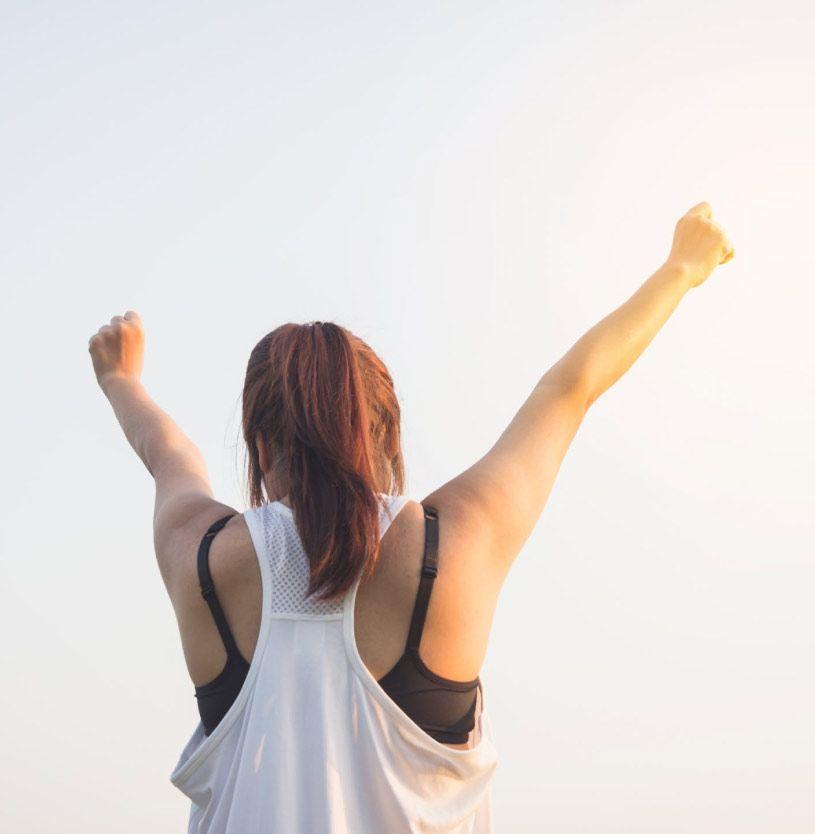 Una chica joven, de espaldas, levantando los brazos a modo de victoria